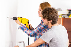 Couple renovating together as woman using power Royalty Free Stock Photography
