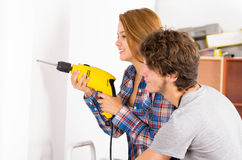 Couple renovating together as woman using power Royalty Free Stock Images
