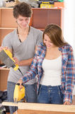 Couple renovating with tools as woman using jigsaw Royalty Free Stock Photography