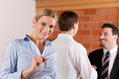Couple renting apartement from realtor. Couple renting apartment from a realtor - a women is happy about it and stands in the front while in the back the men Stock Photo