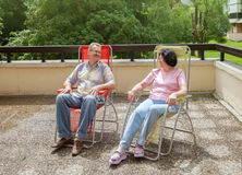 The couple rest in lounge on terrace Stock Photo