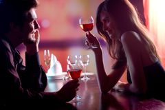 Couple at restaurant. Young couple sharing a glass of red wine in restaurant, celebrating or on romantic date. Focus on woman with glass Stock Image