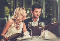 Couple in a restaurant. Cheerful couple with menu in a restaurant royalty free stock image