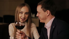 Couple in a restaurant drinking red vine. Romantic young couple at restaurant table toasting stock footage