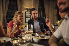 Couple At A Restaurant Meal. Mid adult couple are socialising over a meal in a restaurant. They are eating starters and drinking champagne while laughing and Stock Images