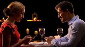 Couple in restaurant using smartphones, dating website concept, acquaintance. Stock photo royalty free stock image