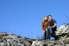 Couple - Resting. Young woman and man sitting on rocks. A lot of blue sky could be your copy space Stock Photo
