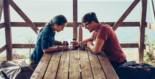 Couple resting in arbor on coast. Young loving couple resting in arbor and looking something at smartphone in summer outdoor Royalty Free Stock Photo