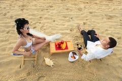 Couple resting on the beach Stock Photos