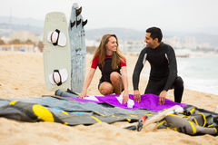 Couple resting on the beach with kiteboard. Smiling couple resting on the beach with kiteboard Royalty Free Stock Image
