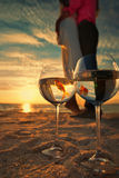 Couple resting on the beach. Reflection of holding bride and groom in wine glasses with golden fishes royalty free stock image