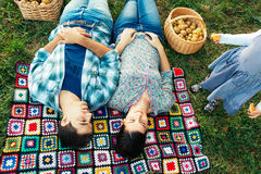 Couple resting on a blanket on the grass in autumn and todler de Royalty Free Stock Images
