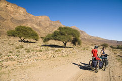 A couple resting during a cyclist tour in Morocco Stock Image