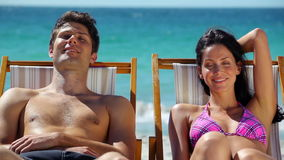 Couple resting on deck chairs stock video footage
