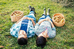 Couple resting on the grass in autumn after picking apples Royalty Free Stock Images