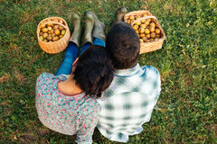 Couple resting on the grass in autumn after picking apples Royalty Free Stock Photos