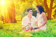 Couple resting on grass in park Stock Images