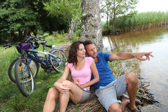 Couple resting by a lake. Couple resting after a bicycle ride stock photos