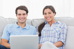 Couple resting with a laptop. Sat on a couch stock photo