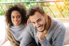 Couple resting and looking into a camera. Face of a guy and his happy girlfriend sitting on a couch, selective focus Stock Photo