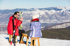 A couple is resting on lounges in picnic zone on european ski resort Stock Image