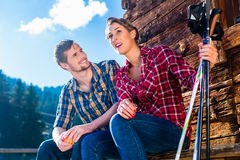 Couple resting from nordic walking in mountain cabin Royalty Free Stock Image