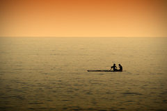A couple resting while paddleboarding in a calm sea at sunset time. Dark orange atmosphere. Empty copy space for Editor`s text Stock Image