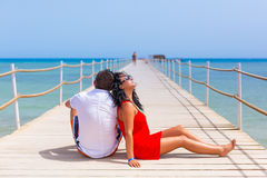 Couple resting on the pier of Red Sea Stock Images