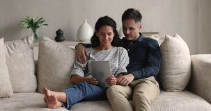 Couple resting on sofa holding tablet having fun using application