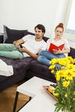 Couple Resting on the Sofa at the Living Room. Young Couple Resting on the Sofa at the Living Room While the Man is Watching TV and Woman is Reading a Book Royalty Free Stock Photography