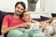 Couple Resting on the Sofa at the Living Room. Young Couple Resting on the Sofa at the Living Room While the Man is Watching TV and Woman is Reading a Book Royalty Free Stock Photo