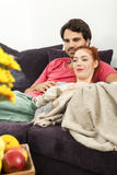 Couple Resting on the Sofa at the Living Room. Young Couple Resting on the Sofa at the Living Room While the Man is Watching TV and Woman is Reading a Book Stock Photography
