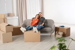 Couple resting on sofa near moving boxes in their stock photo