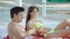 The couple resting, speaking on a beach, clinking glasses and drinking cocktails. 4K stock video