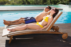 Couple resting on sun loungers by swimming pool Royalty Free Stock Photography