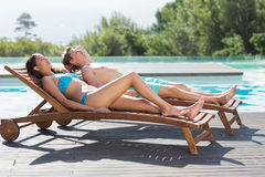Couple resting on sun loungers by swimming pool Royalty Free Stock Photo