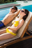 Couple resting on sun loungers by swimming pool Stock Photos