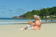 Couple resting  at tropical beach. Happy elderly couple resting  at tropical beach Stock Photos