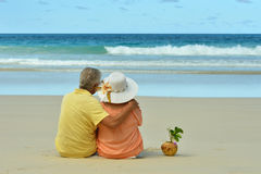 Couple resting  at tropical beach. Happy elderly couple resting  at tropical beach Stock Images