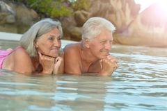 Couple resting  at tropical beach. Happy elderly couple resting  at tropical beach Royalty Free Stock Photos