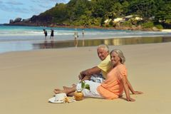Couple resting  at tropical beach. Happy elderly couple resting  at tropical beach Stock Image