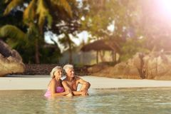 Couple resting  at tropical beach. Happy elderly couple resting  at tropical beach pointing with finger Royalty Free Stock Images