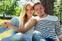 Couple resting under a tree. Young beautiful couple resting under a tree Royalty Free Stock Image