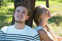 Couple resting under a tree. Young beautiful couple resting under a tree Royalty Free Stock Photography