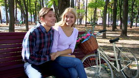 Couple with retro bike in the park on bench. Yong couple with white retro bike in autumn park. Romantic date on park bench. Man tenderly holds her hand and said stock video footage