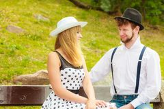 Couple retro style sitting on bench in park Royalty Free Stock Photos