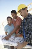 Couple Reviewing Blueprint With Male Contractor Royalty Free Stock Photo