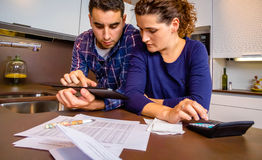Couple reviewing their accounts with a digital Royalty Free Stock Image