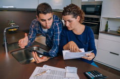 Couple reviewing their accounts with a digital Royalty Free Stock Photos