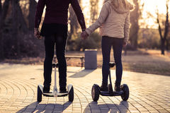 Couple Ride Electrical Scooter Outdoors Autumn Park Man And Woman On Gyroscooter Holding Hands Back Rear View Stock Photography